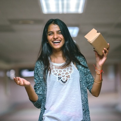 A girl holds a cardboard headset while smiling
